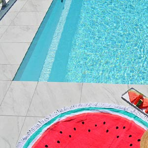Carrara Marblano tiles shown around a pool