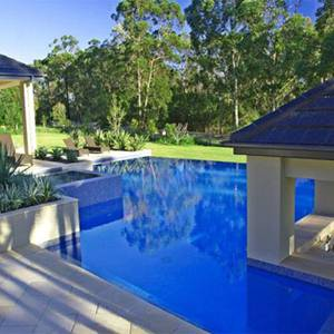 Nice exterior photo of a pool tiled with GC175 Sapphire Gold glass mosaic tiles