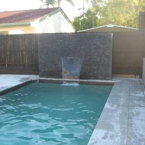 SS017 Black Quartzite Walling used as feature wall beside pool with water cascade